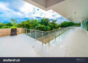 stock-photo-perspective-of-the-modern-glass-and-steel-balcony-deck-patio-promenade-railing-exterior-389392951